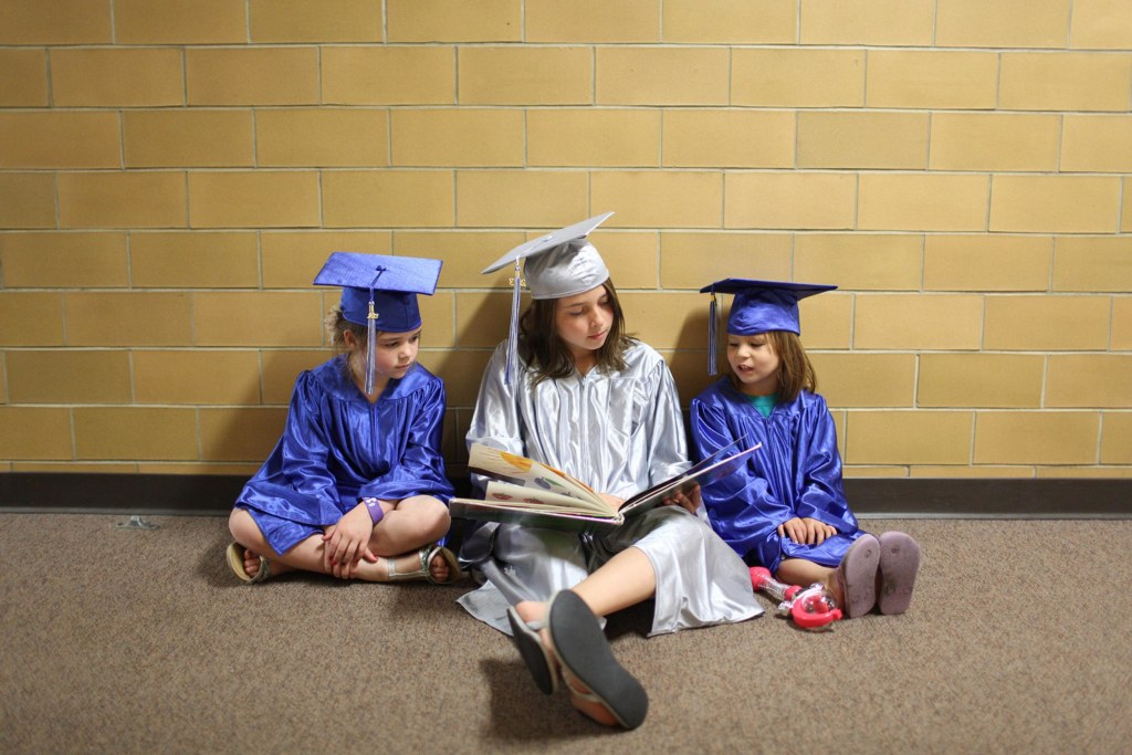 Image: Three students dressed in graduation caps and gowns sit and read a book at the elementary school in Cyrus, Minn.