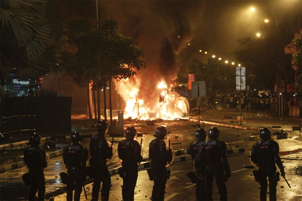 Image: Riot policemen stand guard near a burning vehicle during a riot Singapore's Little India district