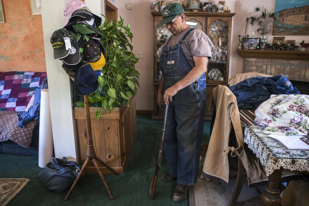 IMAGE: Nucla Town Board member Les Mahana shows one of his guns at his home in Nucla