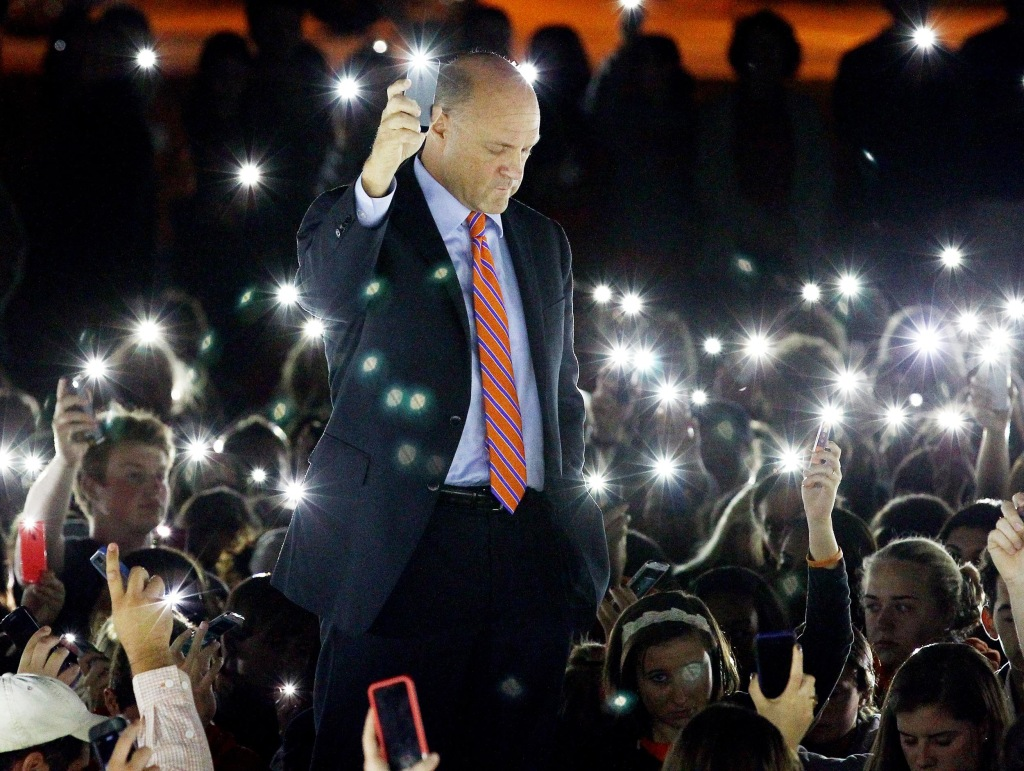Image: Jim Clements, president of Clemson University, leads a moment of silence during a vigil for Tucker Hipps as people use their cell phones to illuminate Bowman Field in Clemson, S.C.