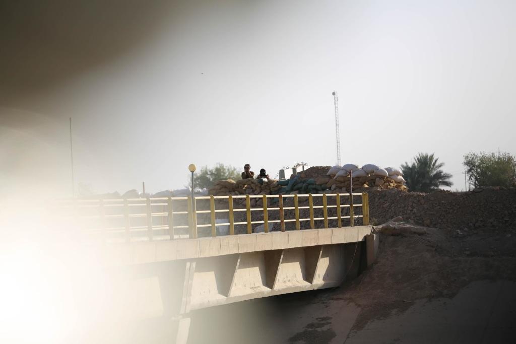"Image: A Kurdish and an ISIS flag on a bridge at the village of ""Mula Abdula"" in Kirkuk, Iraq"
