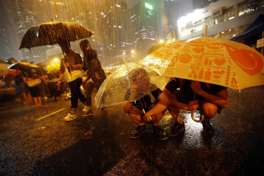 Image: Protesters take shelter from the rain under umbrellas as they block the main street to the financial Central district outside of the government headquarters in Hong Kong