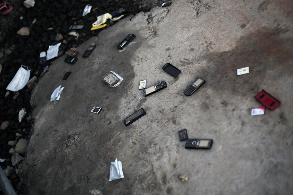 Image:Cellphones are thrown on the ground by patients leaving  the Island Clinic Ebola treatment unit