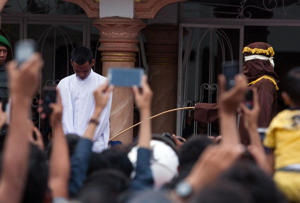 Image: A hooded official (right, wearing brown) caning a man in Banda Aceh