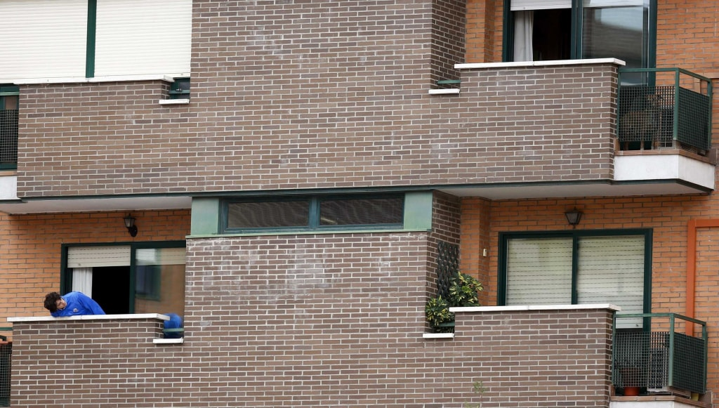 Image: Neighbor tries to get a glimpse of Excalibur, the dog of the Spanish nurse who contracted Ebola, on her apartment's balcony in Alcorcon, outside Madrid
