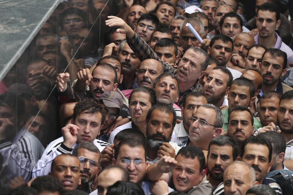 Image: Palestinian Hamas-hired civil servants wait to receive payment outside a post office in Gaza City