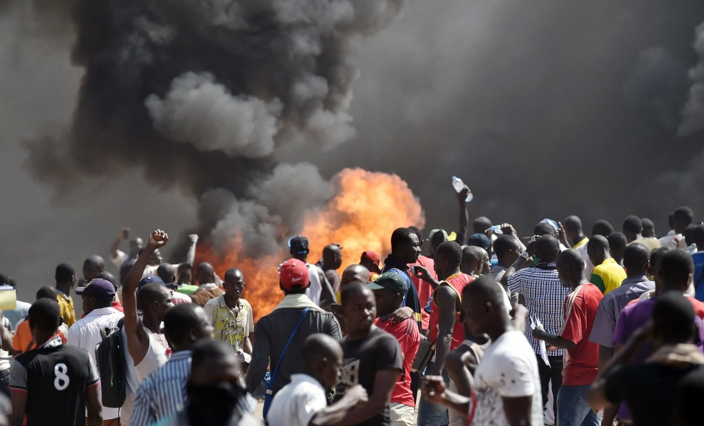 Image: People stand in front of smoke rising from the Burkina Faso's Parliament, where demonstrators set fire to cars