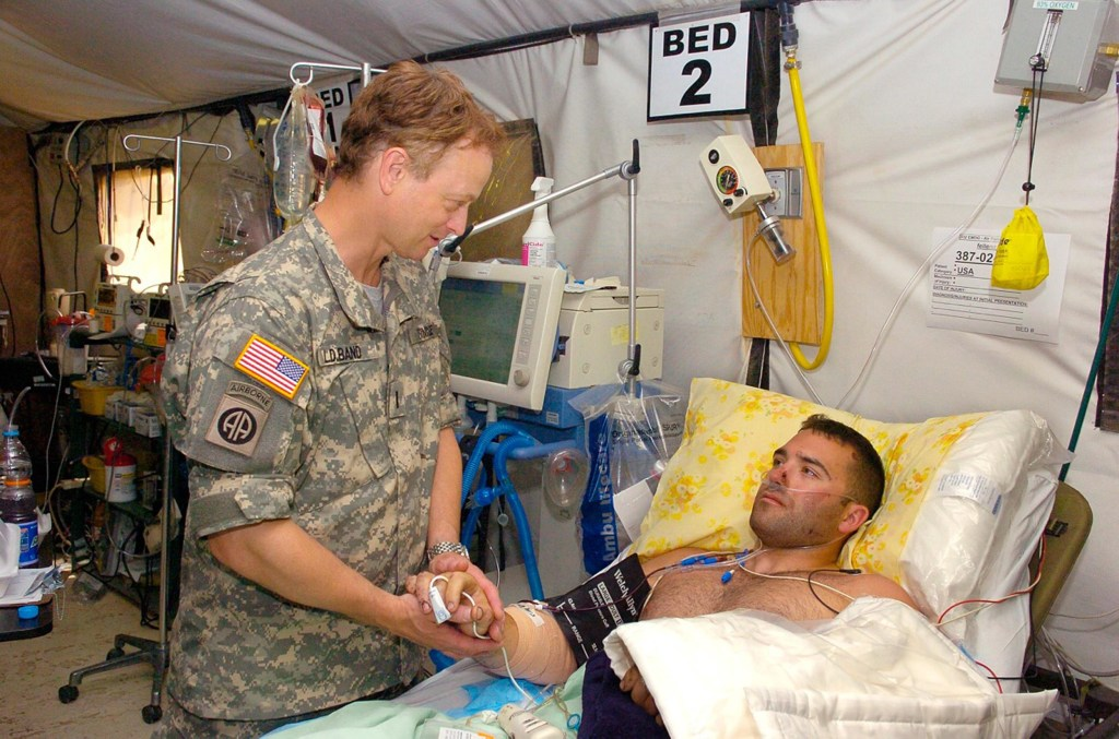 Image: Gary Sinise meets with a wounded soldier.