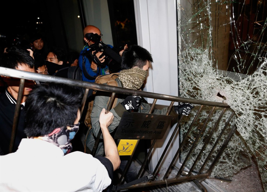 Image: Masked pro-democracy protesters try to break  with a fence a glass window of the Legislative Council in Hong Kong