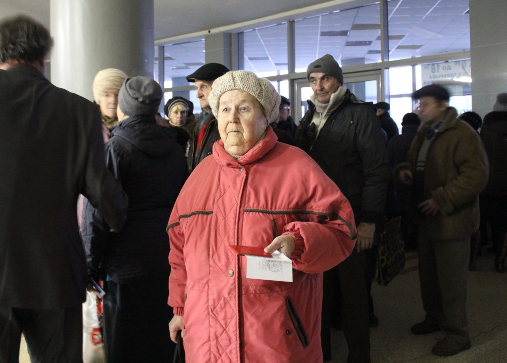 80-year-old Tamara waits in line to receive a food donation at a former circus in the city of Donetsk.