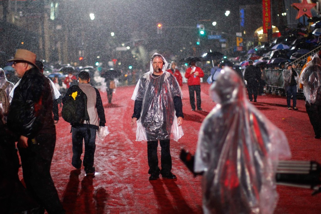 Image: Rain falls on production crew members preparing to start the 83rd Annual Hollywood Christmas Parade in the Hollywood section of Los Angeles