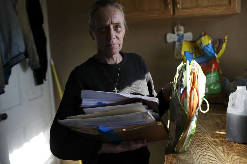 Image: Donna Cox goes through a pile of paperwork and bills at her home in Cleveland, OH
