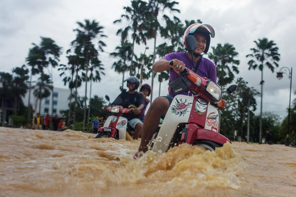 Image: Local residents use their motorbikes to maneuver through floodwaters