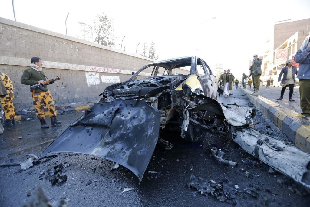 Image: Policemen look at the wreckage of a car at the scene of a car bomb outside the police college in Sanaa