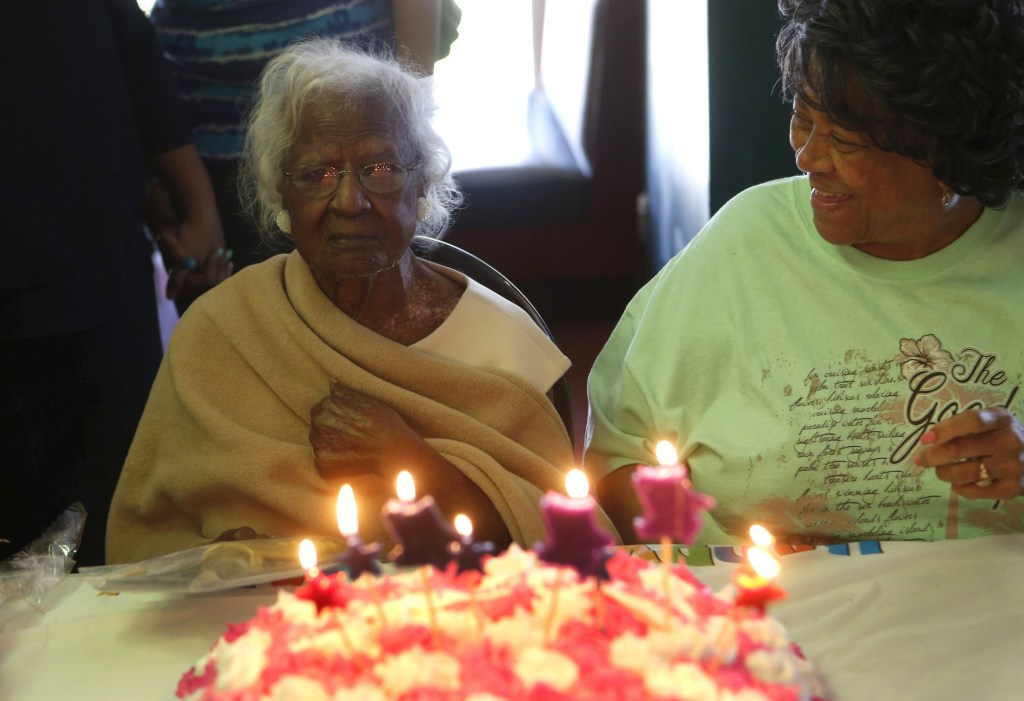 Image: Jeralean Talley, the world's oldest-known living person, looks at the candles on her cake while family and friends sing
