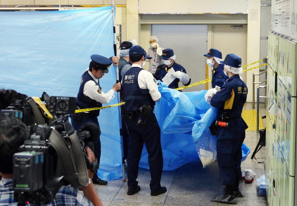 Image:  Police officers inspecting a locker at the Tokyo station