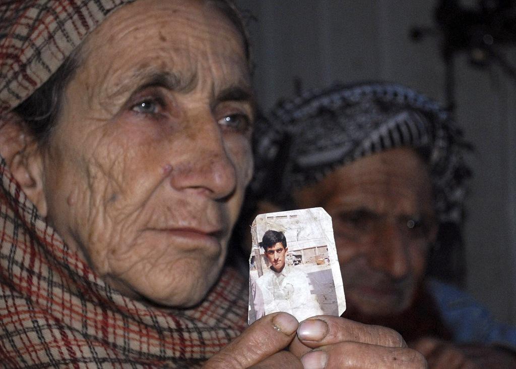 Image: Makhni Begum holds a photograph of her son Shafqat Hussain