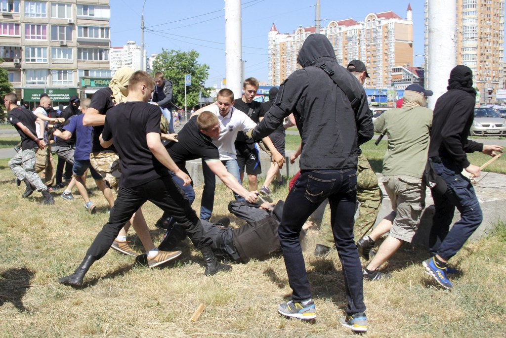Image: Anti-gay protesters attack a policeman during a march organized by LGBT community in Kiev