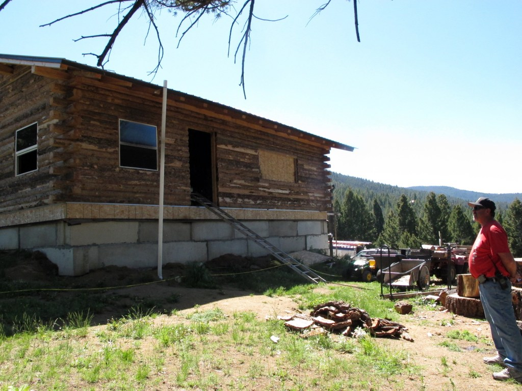 Image: Detective Steve Barclay stands in front of a fire-damaged cabin in the Beaverhead-Deerlodge National Forest outside Deer Lodge, Mont., on Monday, June 8, 2015, where a Montana man shot and killed his wife and three children Sunday morning