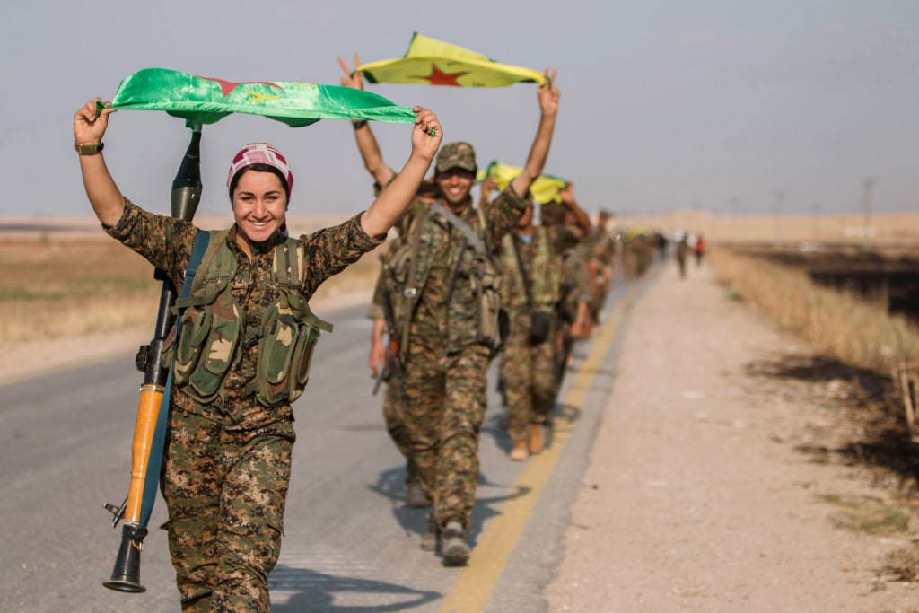 Image: Kurdish fighters gesture while carrying their parties' flags in Tel Abyad of Raqqa governorate after they said they took control of the area
