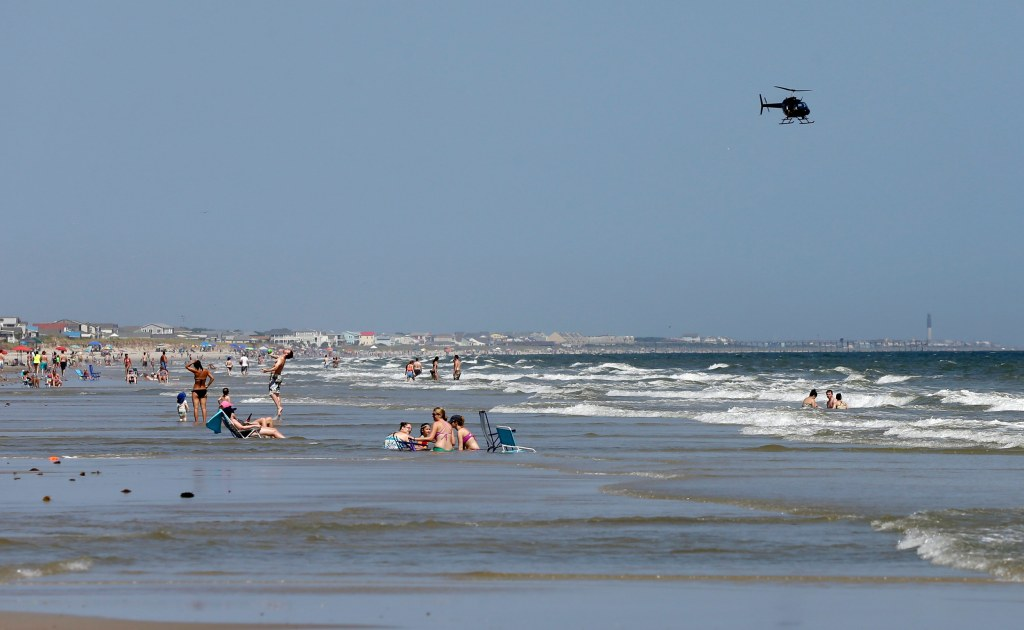 Image: A helicopter flies close to the water as vacationers relax on the beach in Oak Island, N.C.
