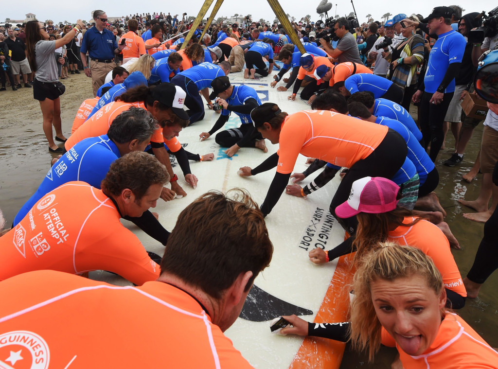 Image: A surfboard is waxed as sixty six surfers from Huntington Beach prepare to break the 'Guinness Book of Records' record
