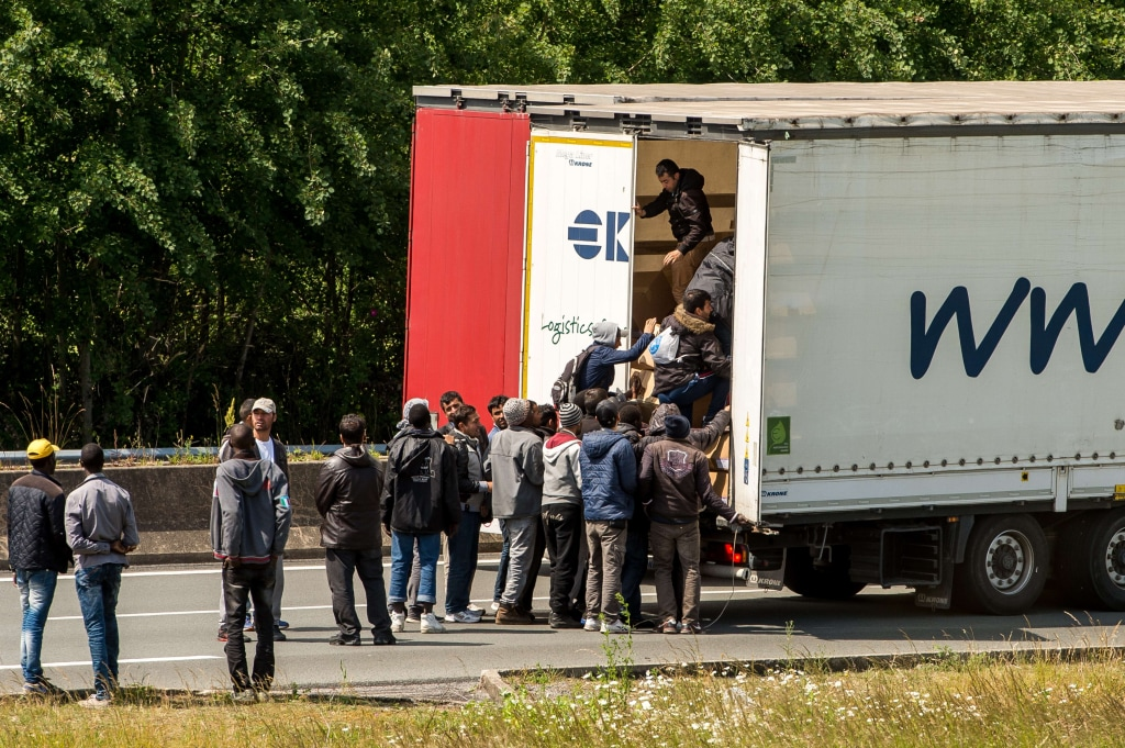 Image: Migrants climb in the back of a lorry on a highway leading to the Channel Tunne in Calais, northern France, Tuesday.