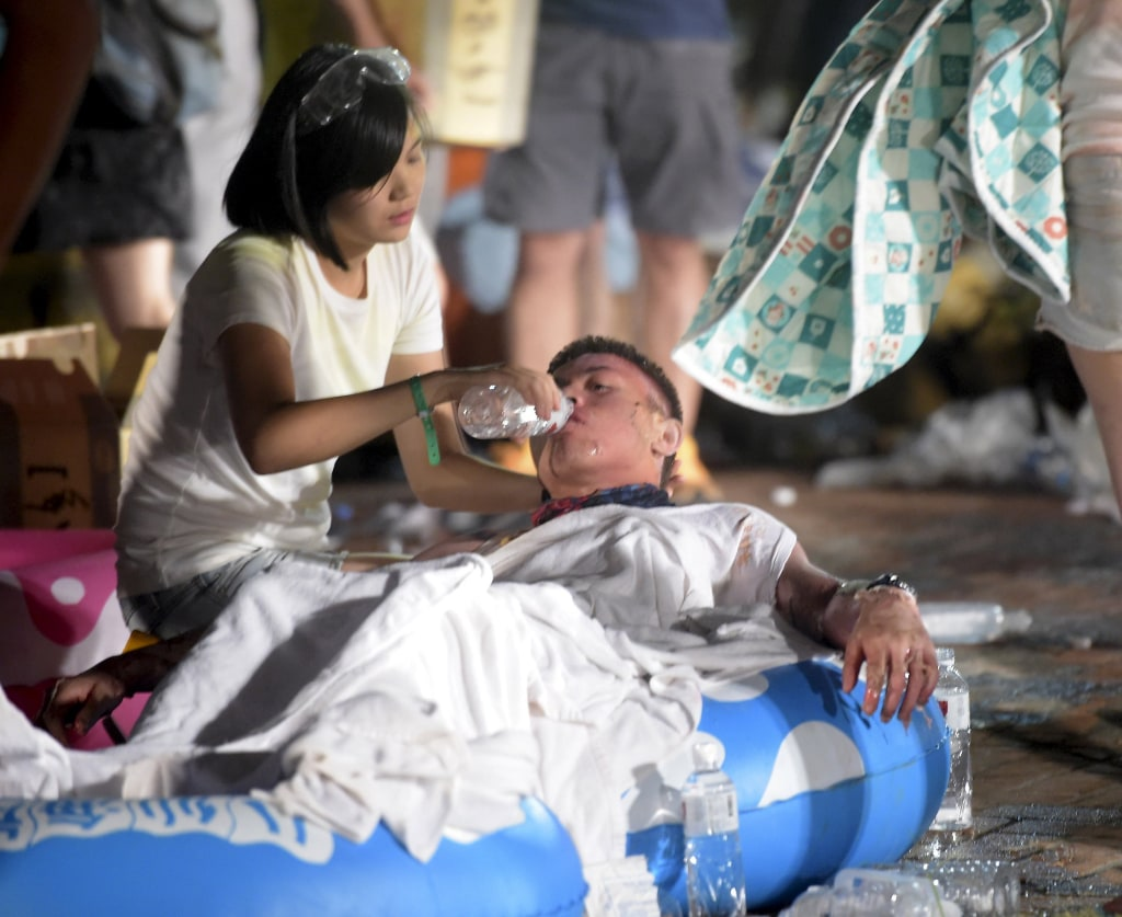 Image: A person helps an injured victim from an accidental explosion during a music concert at the Formosa Water Park in New Taipei City