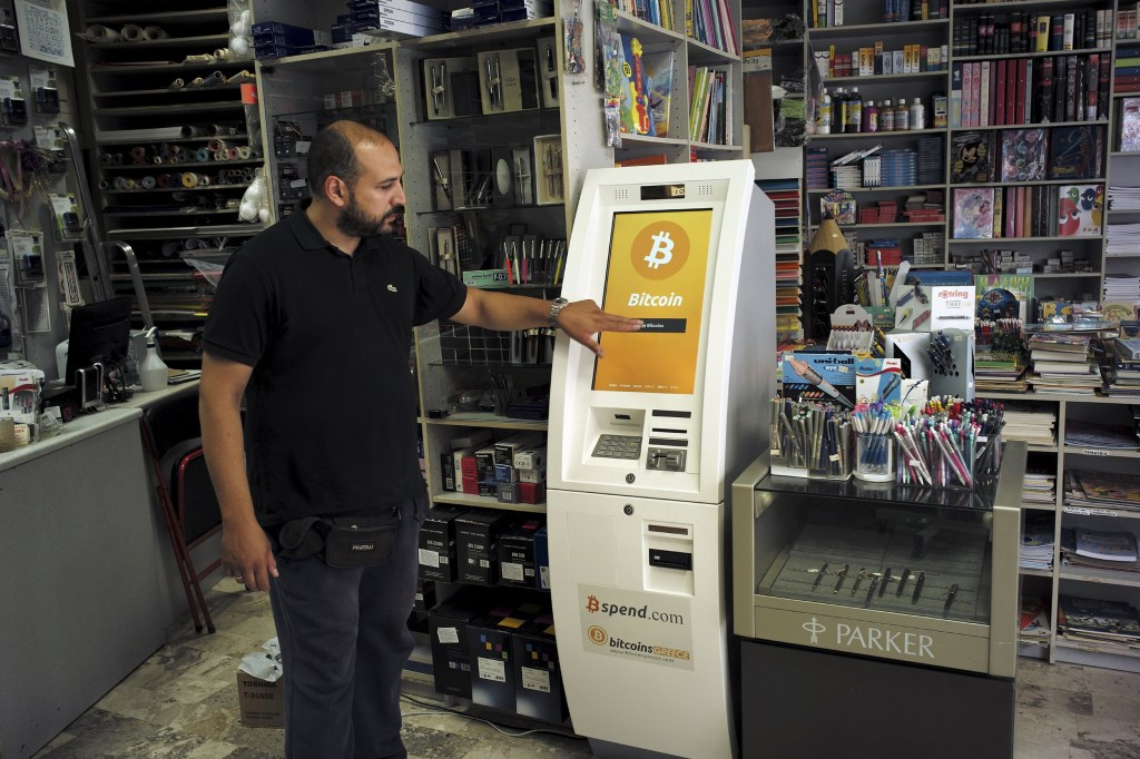 Image: A man demonstrates the use of a Bitcoin ATM at a bookstore in Acharnai in northern Athens, Greece