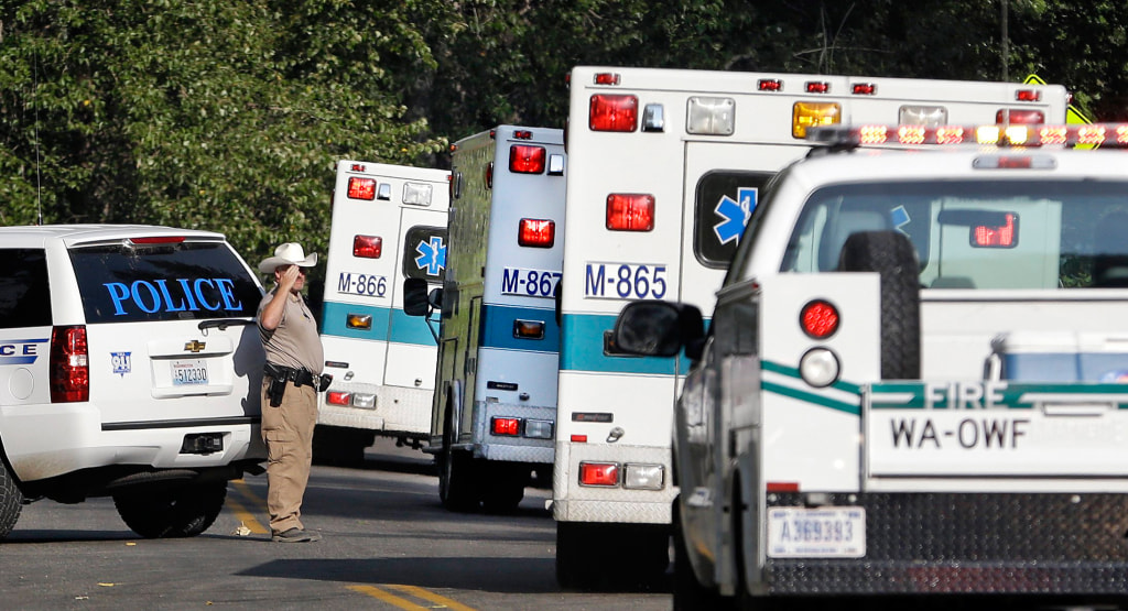 Image: Twisp Police Chief Paul Budrow salutes as ambulances carry the bodies of three firefighters