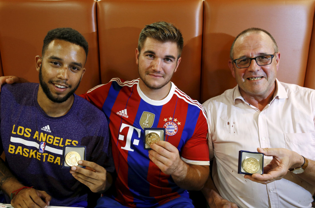Image: Sadler, Sharlatos, and Norman, three men who helped to disarm an attacker on a train from Amsterdam to France, pose with their medals at a restaurant in Arras, France