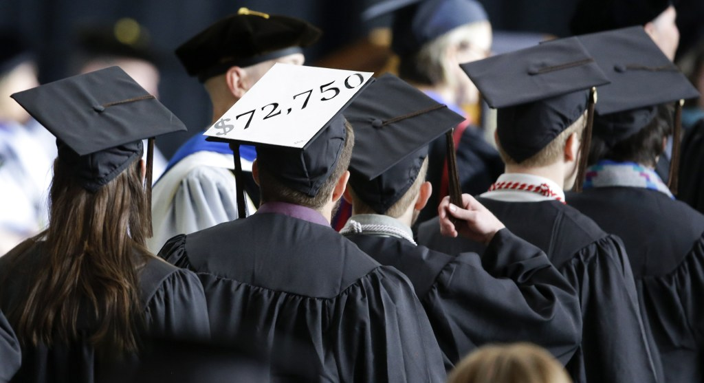 Image: A student in line for his diploma wears a cap decorated with the cost of his education during graduation ceremonies at the University of Idaho in Moscow, Idaho