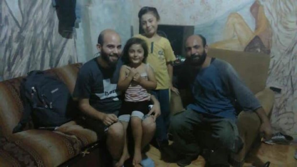 Image: Syria refugee Abdul (right), with son Abdelillah, 9, and daughter Reem, 4, and an activist