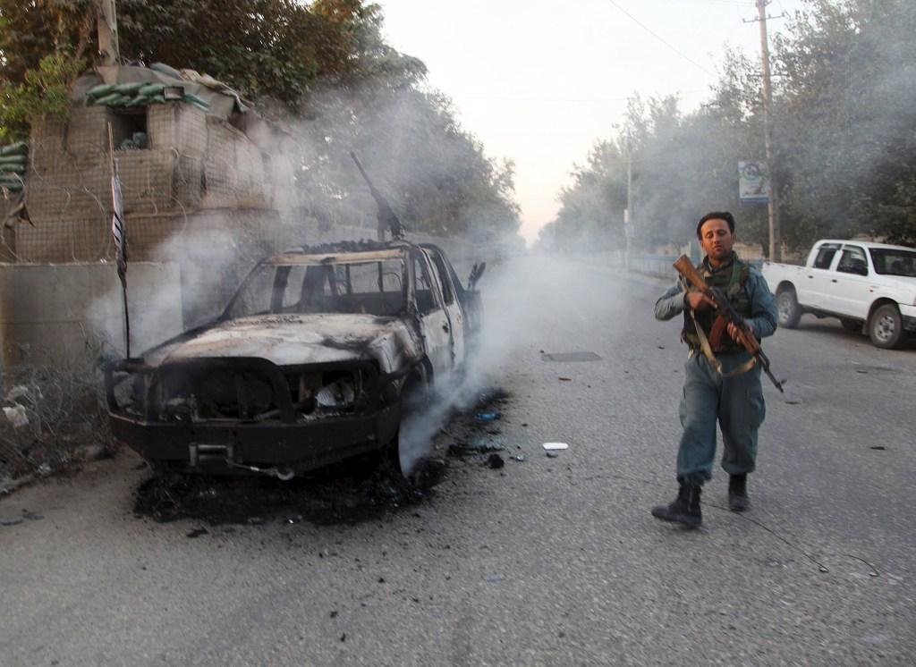 Image: An Afghan police officer patrols near burning car in Kunduz