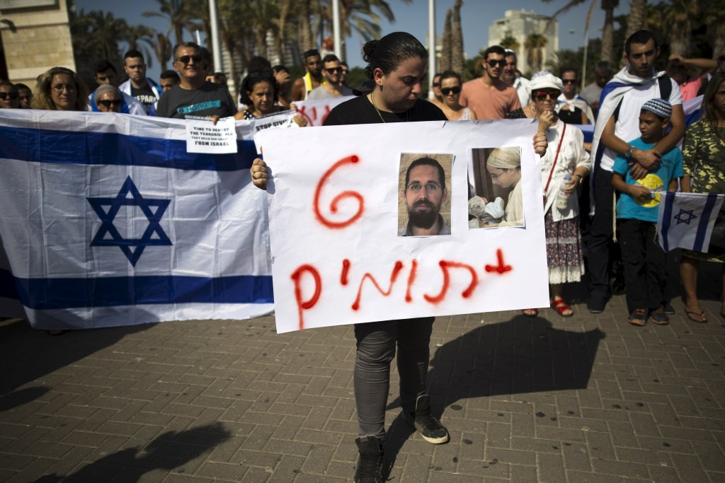 """Image: A woman holds a placard that reads in Hebrew """"Plus 6 orphans"""" and depicting the pictures of Eitam and Naama Henkin"""
