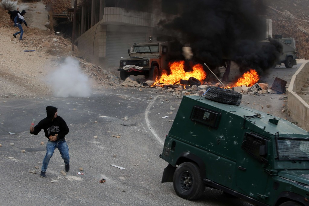 Image: A protester throws a bottle at Israeli security forces vehicles