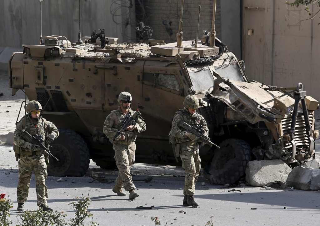 Image: NATO soldiers walk in front of a damaged NATO military vehicle at the site of a suicide car bomb blast in Kabul