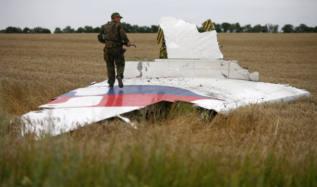 Image: Armed pro-Russian separatist stands on part of the wreckage of the Malaysia Airlines Boeing 777 plane after it crashed near the settlement of Grabovo in the Donetsk region
