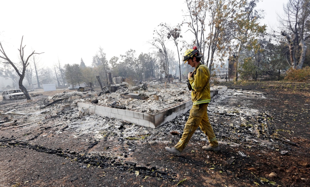Image: A firefighter walks past the remains of a house destroyed in a wildfire