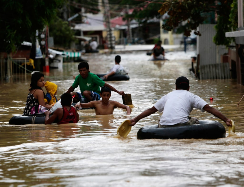 Image: Filipino typhoon victims wade in flood water