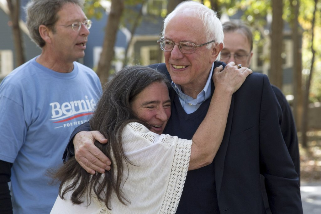 Image: U.S. Democratic presidential candidate Bernie Sanders is hugged by supporter Gerhild Krapf before talking to supporters at a fundraising house party at the home of Krapf and Michael Brau in Iowa City