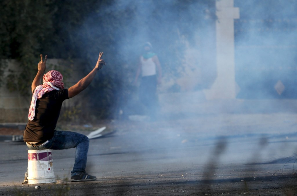 Image:  Palestinian protester sits on a bucket that he used to cover a tear gas canister fired by Israeli troops during clashes near the Jewish settlement of Beit El, near the West Bank city of Ramallah