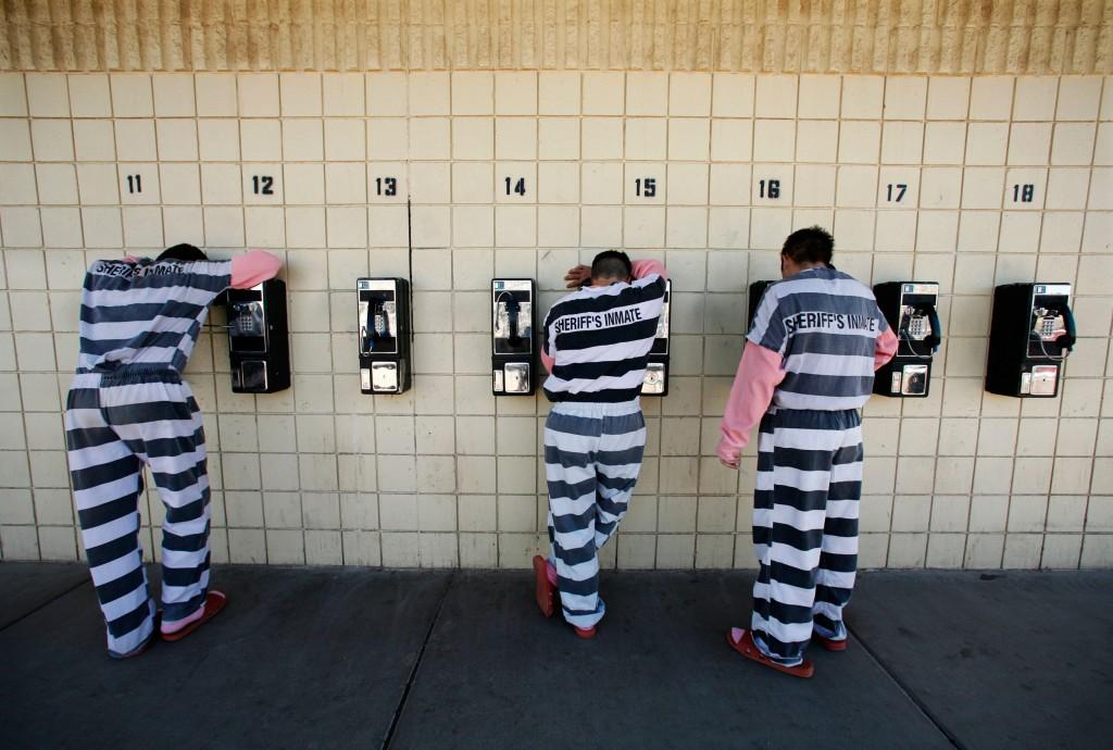 Image: Inmates talk on pay phones at a jail