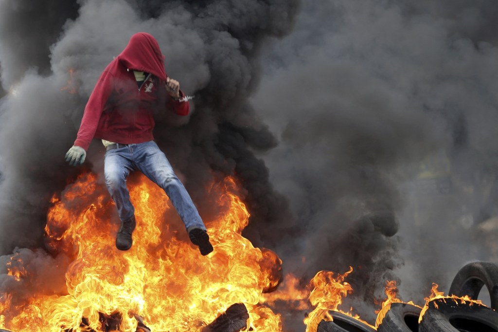 Image: Palestinian protester jumps over burning tyres during clashes with Israeli troops near the Jewish settlement of Bet El, near the West Bank city of Ramallah