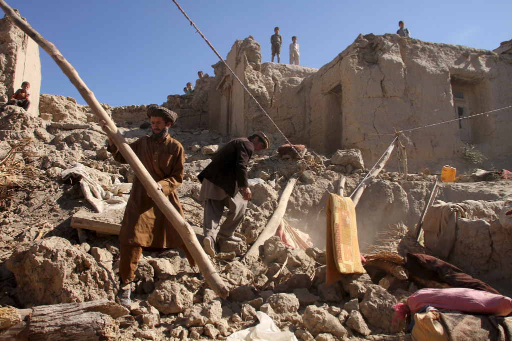 Image: Men look for their belongings after an earthquake, in Kishim district of Badakhshan province, Afghanistan
