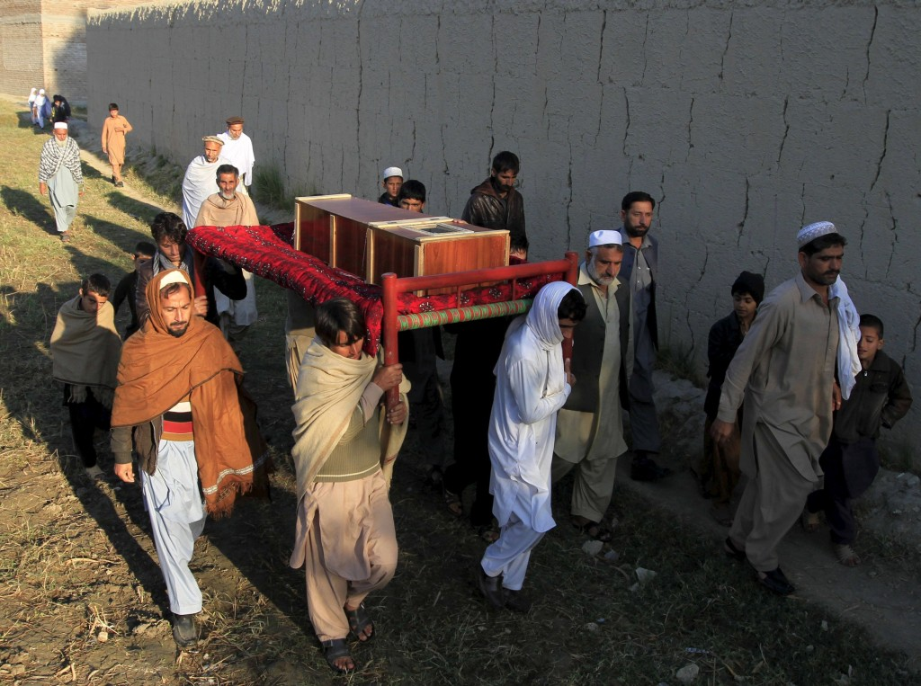 Image: Afghan men carry a coffin of an earthquake victim for burial in Nangarhar province, Afghanistan