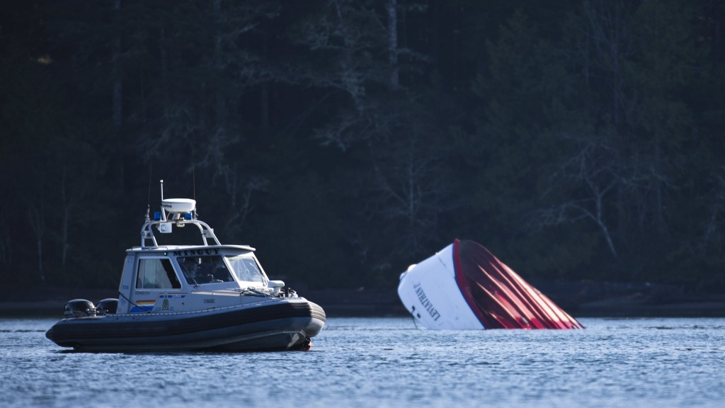 Image: An RCMP boat carrying divers sits beside a capsized whale watching boat in Tofino