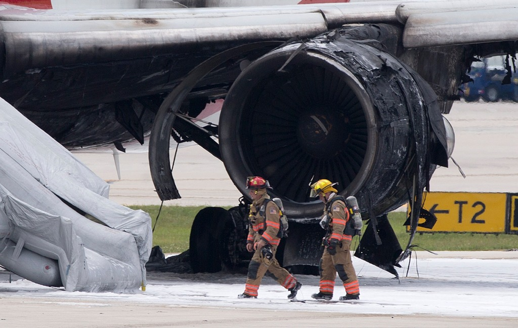 Image: Firefighters walk past a burned out engine