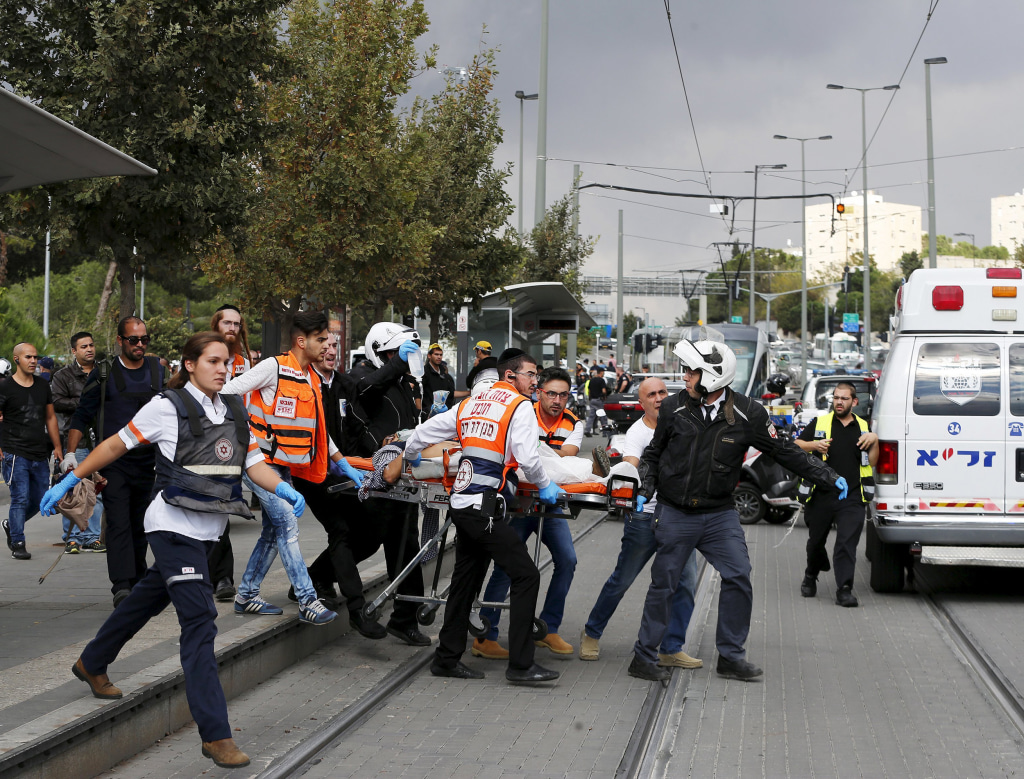 Image: Medics evacuate an Israeli man injured during a stabbing attack in Jerusalem