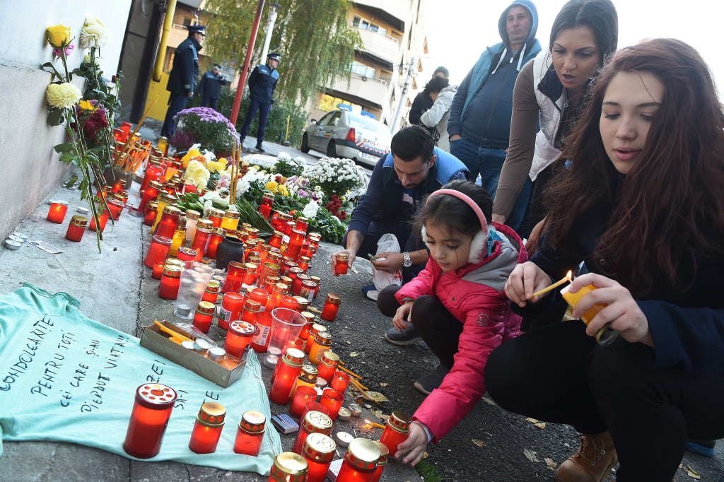 Image: People light candles at a memorial outside the nightclub